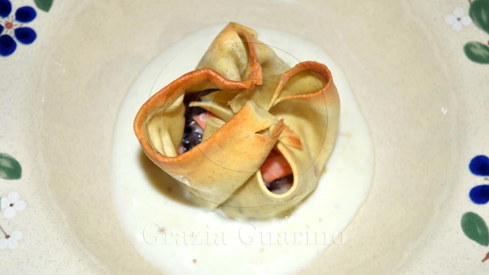 Fagottini di pasta con salmone, radicchio e robiola su fonduta di formaggi